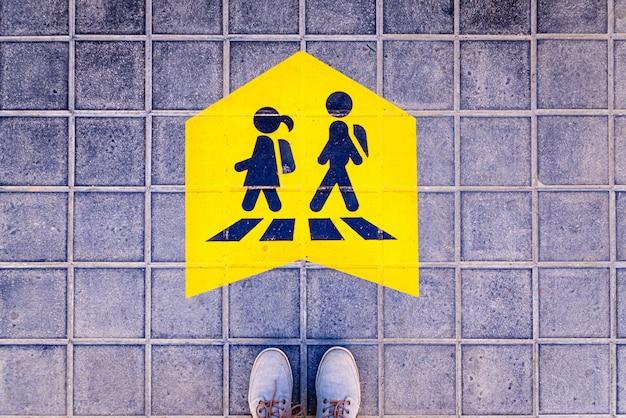路上で学校に行く途中の子供たちに安全な道標を立てる足。