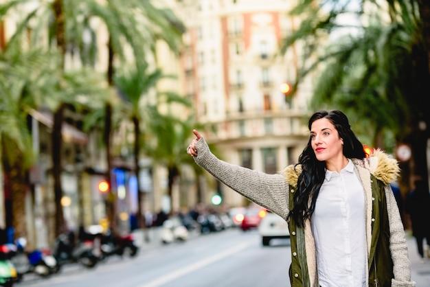 Женщина средних лет приветствует такси с поднятой рукой на улице.