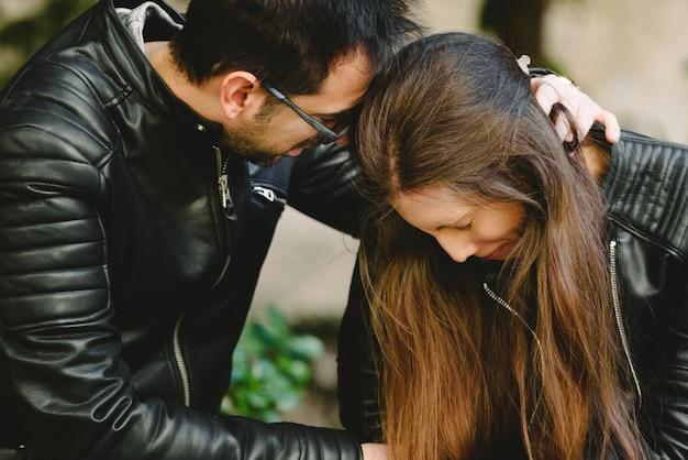 彼のガールフレンドの嫉妬による怒りの主張の後彼の女の子を抱き締める愛情深い彼氏。