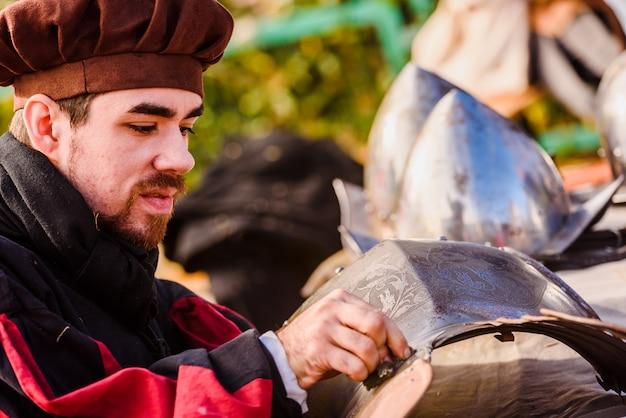 職人は中世の時代を装って汚れた鎧を掃除しました。