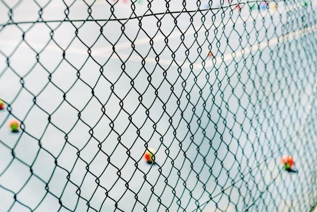 テニスコートの前景に金属製のネットフェンス