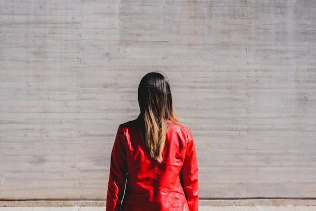 カジュアルなジャケットと彼女の背中に女性
