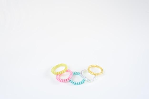 Пластиковые браслеты различных цветов, изолированных в шаблон, расположенных в белом.