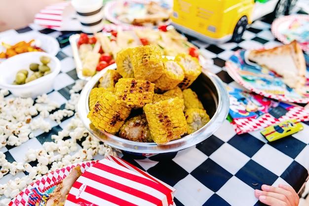 夏の誕生日にトウモロコシを食べている子供たち。