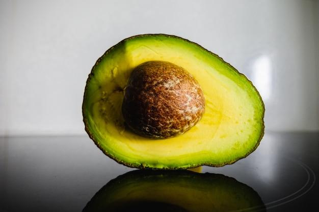Авокадо, сечение, с отражением в черной поверхности кухни.