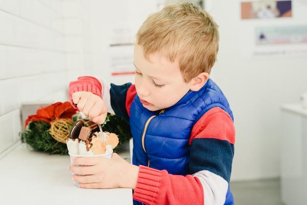 Ребенок дегустирует мороженое и ест его по-детски.