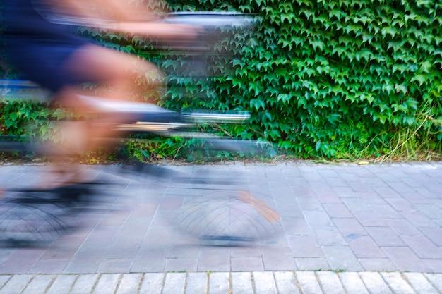 動きがぼやけたサイクリストは、速度を示し、自転車レーンに沿って運転し、輸送と都市の移動をより持続可能にします。