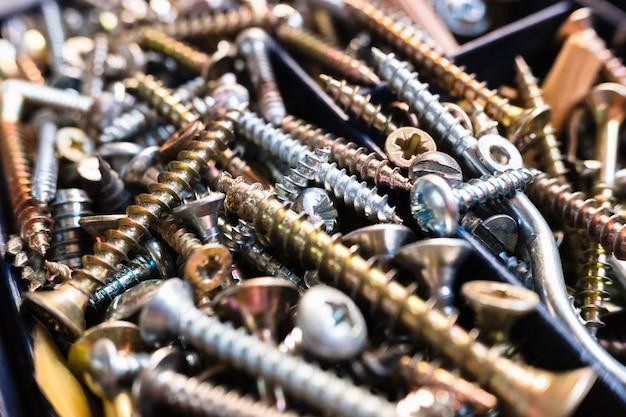 さまざまなサイズの多くの銀と金のネジのマクロ。