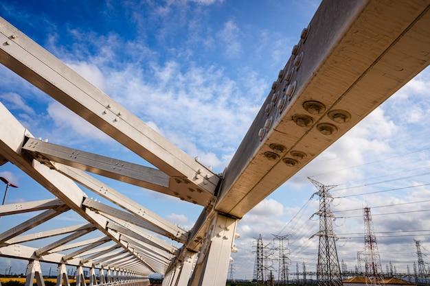 背景の空を背景に、ネジで結合された梁の金属構造。