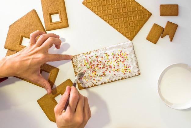 ジンジャーブレッドクッキーを飾る子供の手