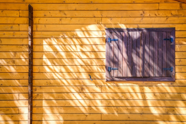 太陽と影で閉じた窓と木の板の家の壁。