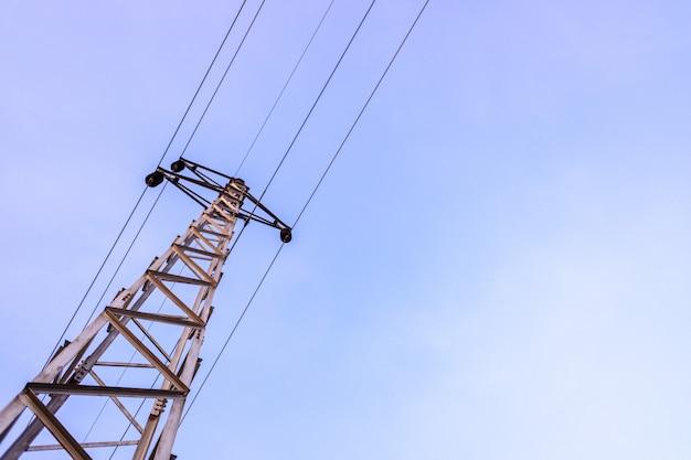 青い空を背景に、高電圧ケーブルの塔