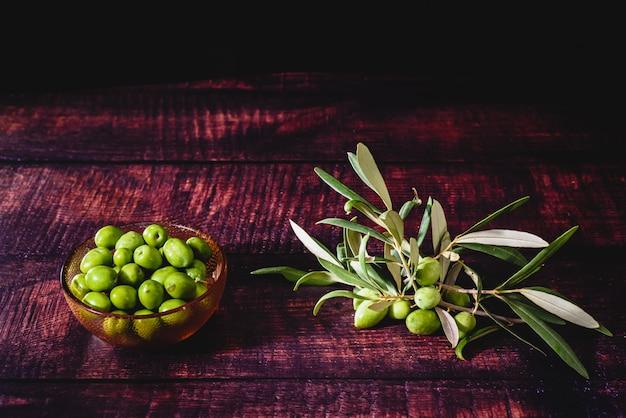 暗い背景、バージンオリーブオイルのソースに分離されたオリーブの木の果実。