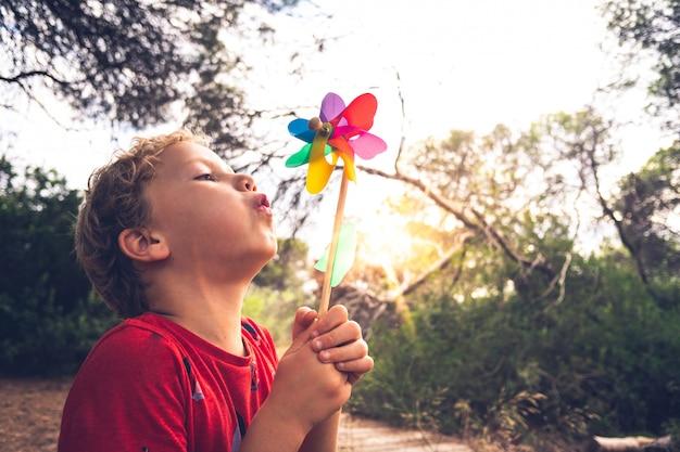 Маленький красивый мальчик дует вертушка в лесу, беззаботный, с выцветшими тонами и в стиле ретро.