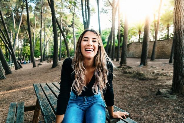 Красивая девушка смеется вслух полный жизни и счастья при выходе из средней школы.