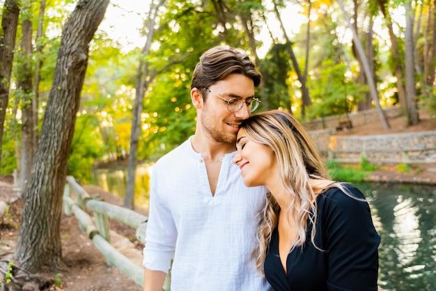 Влюбленная пара делает баловство в парке на закате.
