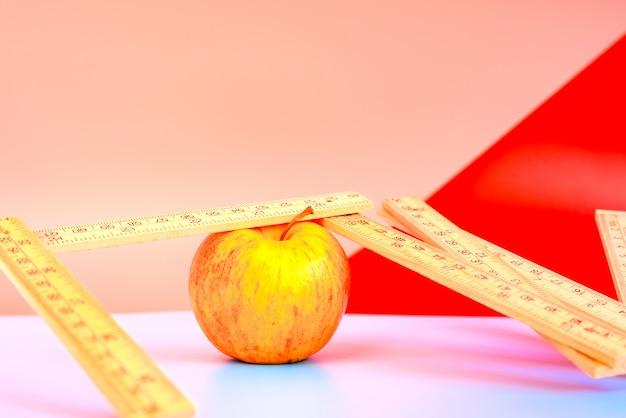 Измеряя лента рядом с яблоком, концепция потери веса с здоровым питанием.