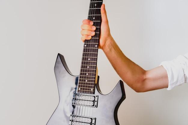 弦を押しながら歌を演奏するギタリストの手のクローズアップ。