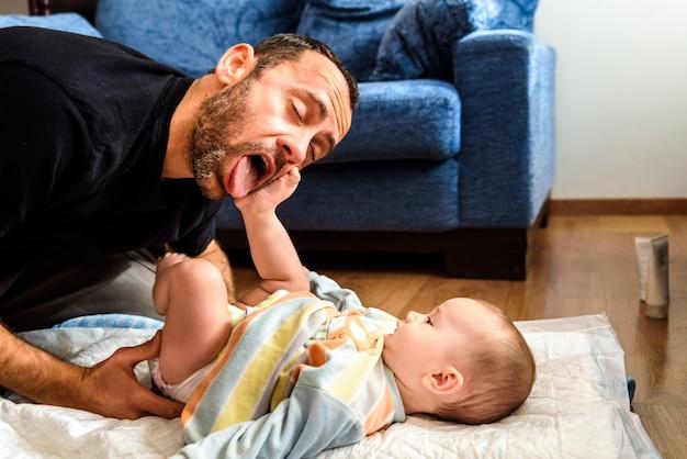お父さんがおむつを変えながら、赤ちゃんの娘に面白いジェスチャーをします。