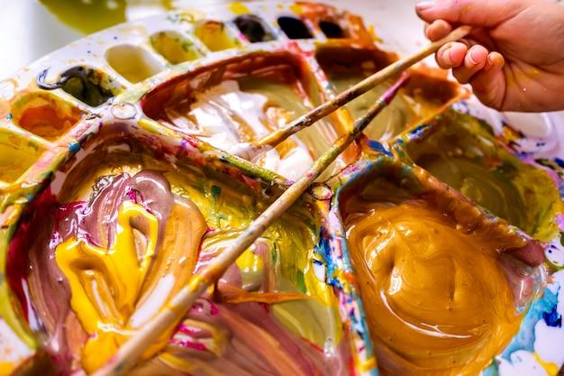 少女はアクリルペイントブラシを使用して、キャンバスに絵を描きます。