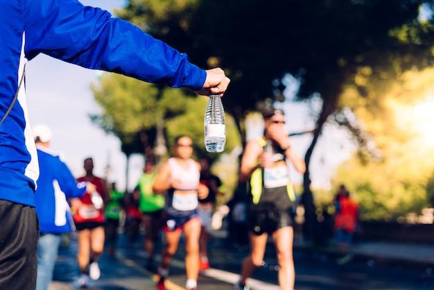 Рука помощи доставляет бутылку воды бегущему в беговой гонке, чтобы он выпил.