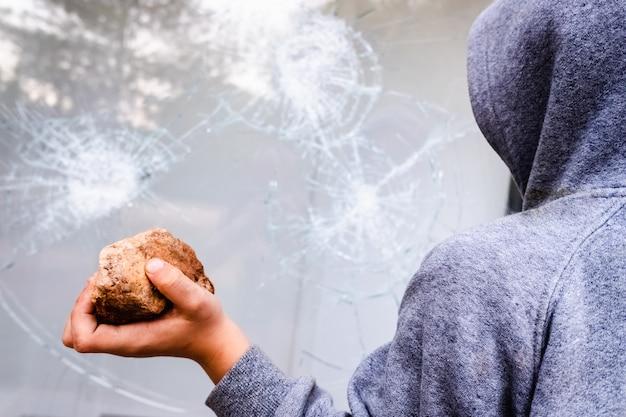 子供は石を手に持ってガラスにぶつけて窓を割る。