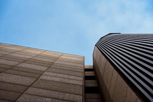 活動のない、落ち着いたブルーの色調とコピースペースを備えたビジネスオフィスビル。