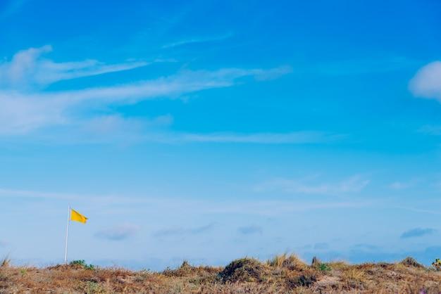 風になびく黄色の布旗