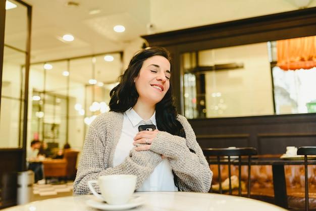 彼女の携帯電話への愛の電話を受けるカフェに座っている女性。