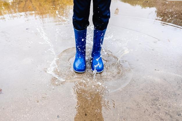 Мальчик прыгает в луже на улице после дождливого дня.