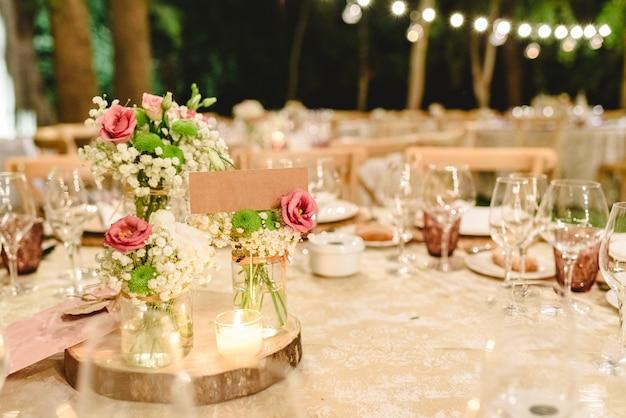 結婚式場のテーブルに豪華なカトラリーでセンターピースを飾る花。