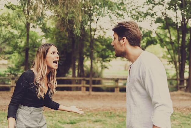 女性は公園で彼女に嫌がらせをする男性に向かって叫びながら自分を守る。