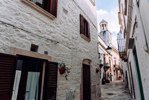 ロコロトンドの典型的なイタリアの都市の白塗りの壁が付いている家のある通り。