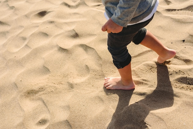 ビーチの砂の上を歩く少年の足。