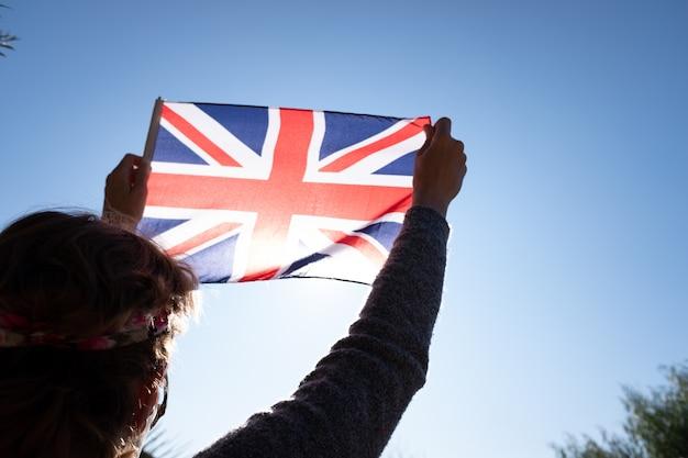 女性は愛国的な瞬間に太陽に対してイギリスの旗を保持しています。