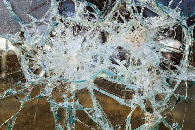 Толстое разбитое стекло окна в заброшенной промышленной зоне.