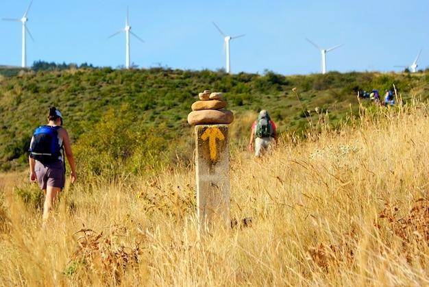 ハイキング巡礼者は、サンティアゴのカミノの兆候を通り過ぎます。