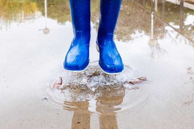 青い長靴のある公園で水たまりに子供が跳ねます。