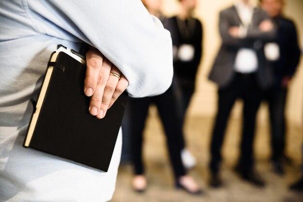 Деталь руки бизнесмена держа бумажную тетрадь.