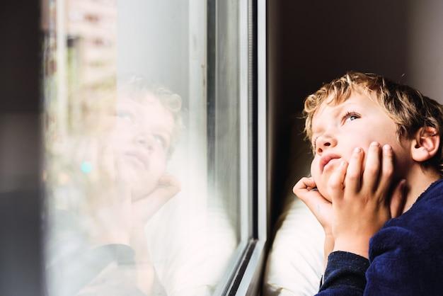Мальчик выглядит скучно в окно