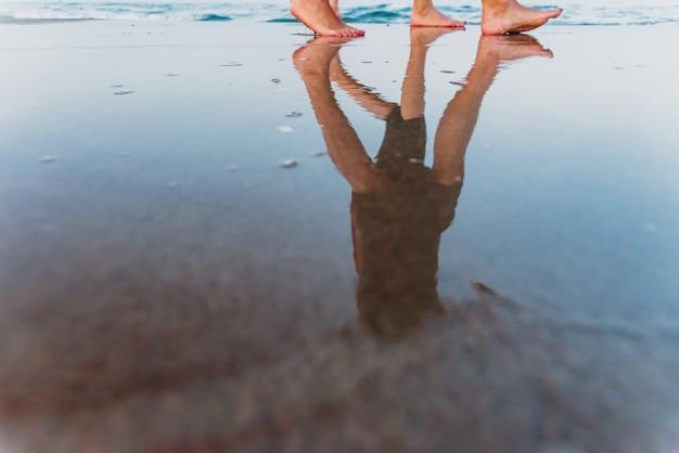 Две девушки гуляют вдоль берега пляжа на закате.
