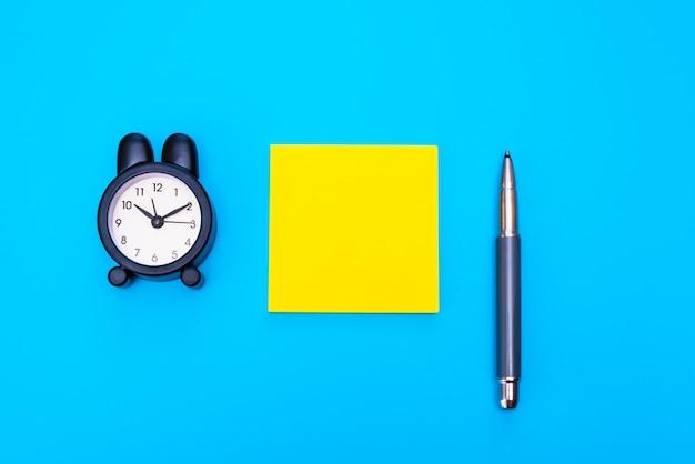 白紙のメモと目覚まし時計がメッセージを書くための平らな紙