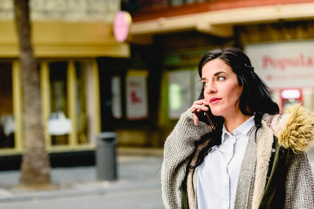 通りで携帯電話で電話に出る中年女性。