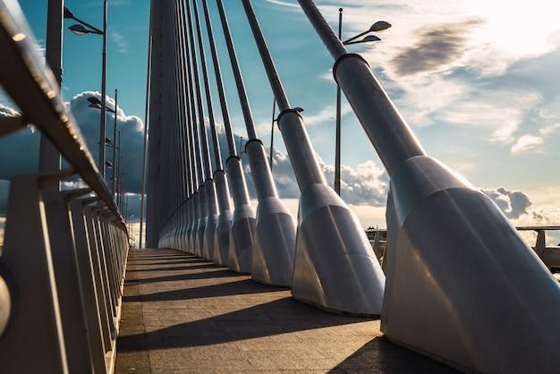 バレンシアの都市橋の歩道のスチールケーブルに劇的に沈む夕日