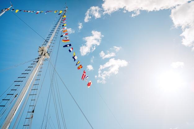 Мачта парусника без вуали с флагами морских знаков, космосом для текста экземпляра.