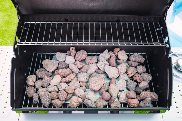 Новый и чистый гриль для барбекю с лавовыми камнями