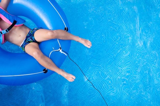 Мальчик плавает в бассейне вид сверху