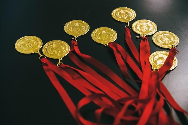 勝者に報酬を与えるための黒いテーブル上のオリンピックの金メダル。