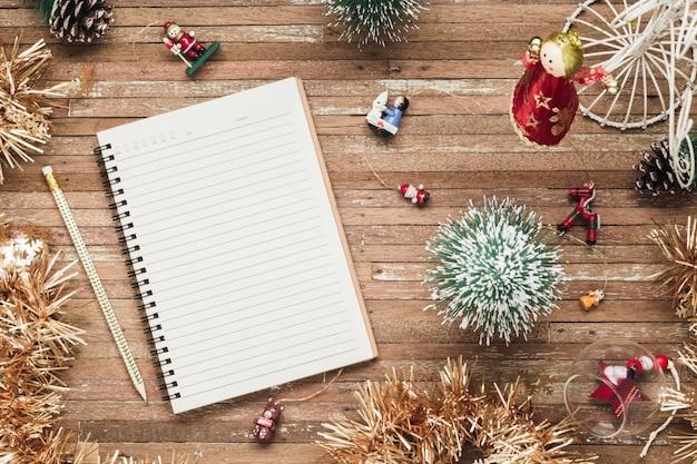 クリスマスの飾りと木の上の空白のノートブック