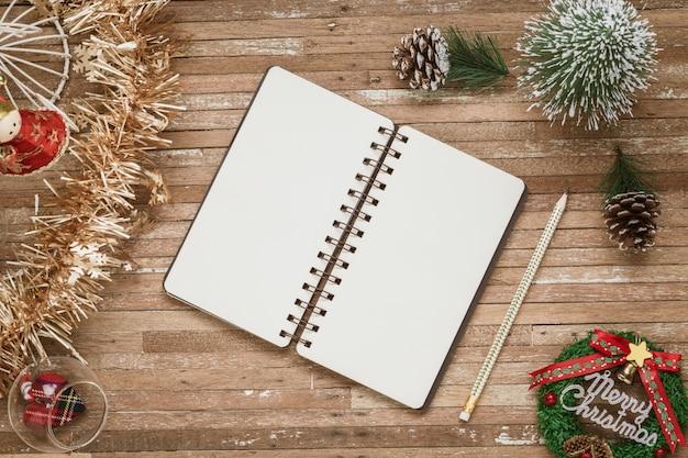 クリスマスの背景の木にモックアップの空白のノートブック